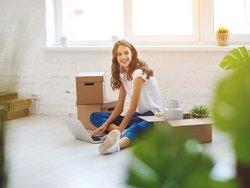 Erste eigene Wohnung, junge Frau sitzt zwischen Umzugskartons  mit Laptop am Boden und lächelt, Foto: JenkoAtaman / stock.adobe.com