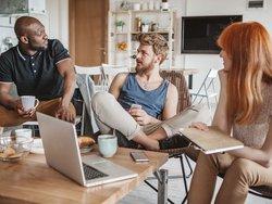 WG-Mietvertrag, Foto von zwei jungen Männern und einer jungen Frau in einem Gemeinschaftsraum beim Unterhalten, Foto: iStock.com / svetikd