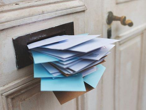 Wettbewerbsrecht, Makler, aufdringliches Anwerben, ein Briefeinwurf quillt über mit Post, Foto: iStock.com / PeopleImages