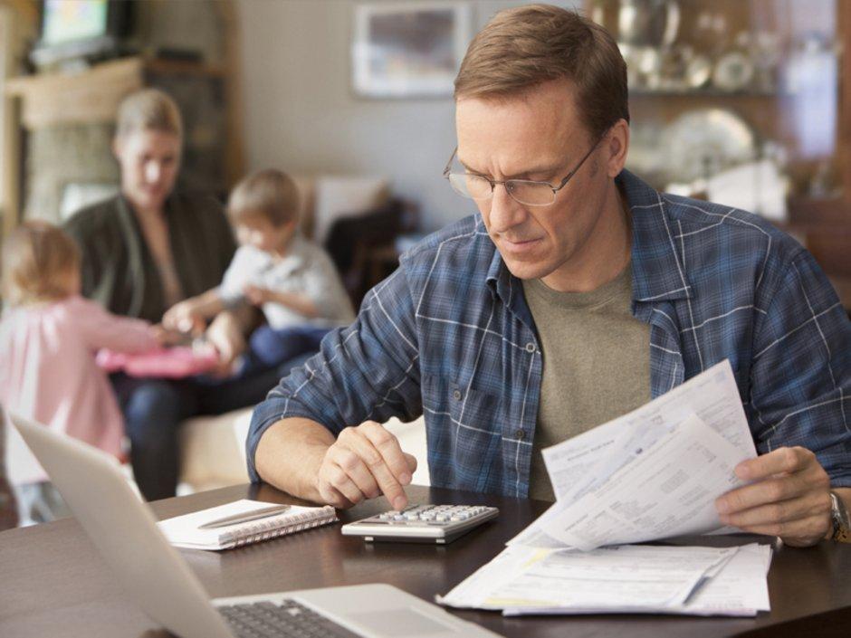 Gebäudeversicherung, Mann tippt auf Taschenrechner und hält Blätter in der Hand, Foto: iStock/SelectStock