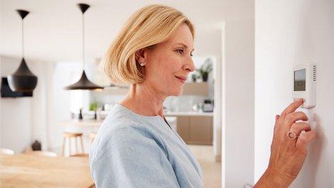 Heizkosten senken, eine Frau gibt an einem digitalen Thermostat die Temperatur ein, Foto: Monkey Business/stock.adobe.com