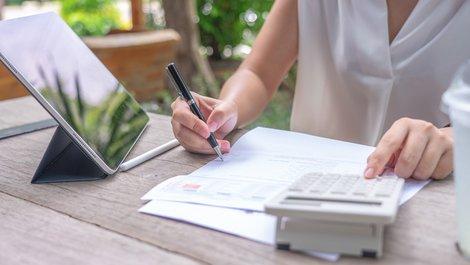 Heizkosten abrechnen, Frau rechnet Werte auf einem Dokument nach, Foto: zasabe / stock.adobe.com