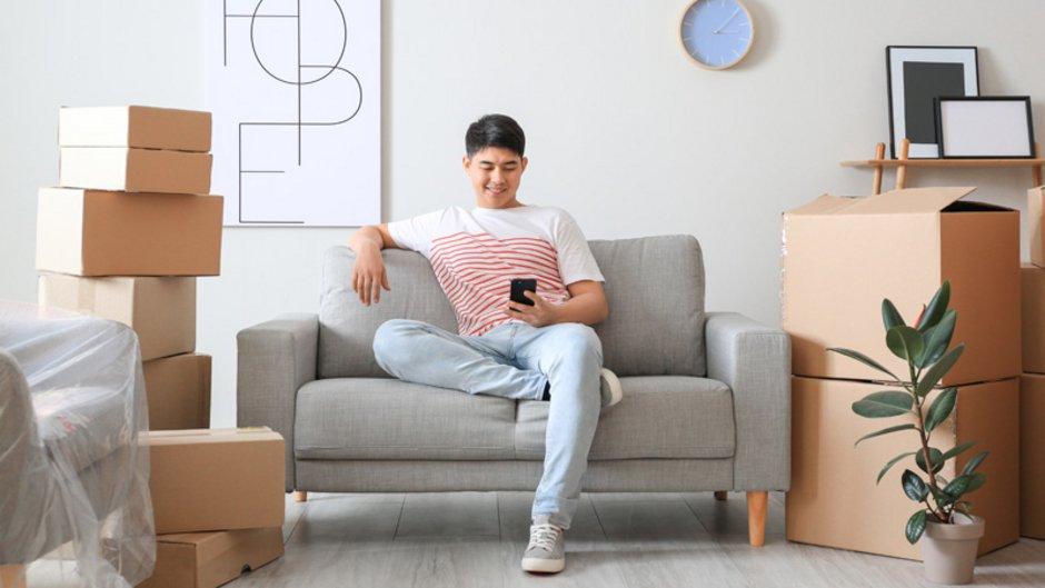 Erste eigene Wohnung, junger Mann sitzt mit dem Handy in der Hand auf kleinem Sofa zwischen Umzugskartons, Foto: Pixel-Shot / stock.adobe.com