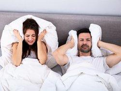 Was Hauseigentümer dulden müssen, Paar liegt im Bett und hält sich Kissen auf die Ohren, Foto: Andrey Popov/stock.adobe.com