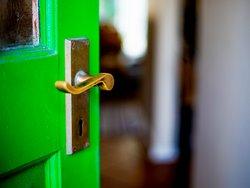 Corona Besichtigungstermin, Corona Wohnungsbesichtigung, eine grüne Türe öffnet sich, Foto: iStock.com/brazzo