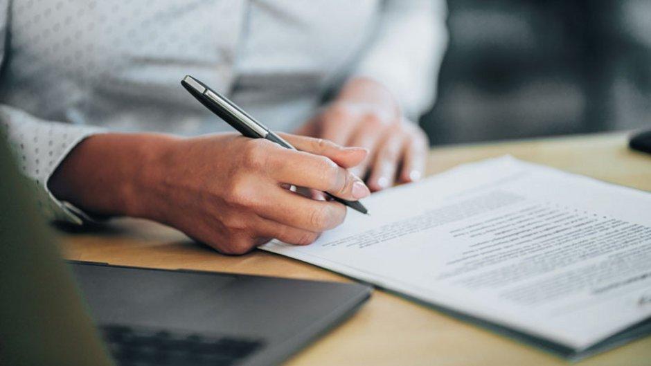 Ein Vertrag und eine Person mit Stift kurz vor der Unterzeichnung, Foto: istock.com / VioletaStoimenova