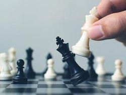 Wettbewerbsrecht, Makler, auf dem Schachbrett schlägt ein weißer König den schwarzen König, Foto: Monster Ztudio / stock.adobe .com