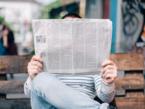 Wettbewerbsrecht, Makler, verschleierte Werbung, ein Mann auf einer Bank liest Zeitung, Foto: Roman Kraft / Unsplash