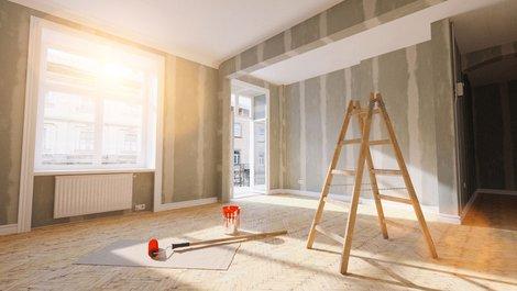 Mieterhöhung, Bild einer Wohnung mit nackten Wänden, einer Leiter und einer Farbrolle in der Mitte, Foto: iStock.com / rclassenlayouts
