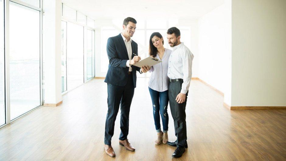 mieten oder kaufen, Bild mit einem Paar bei der Besichtigung einer Wohnung mit einem Makler, Foto: AntonioDiaz / stock.adobe.com