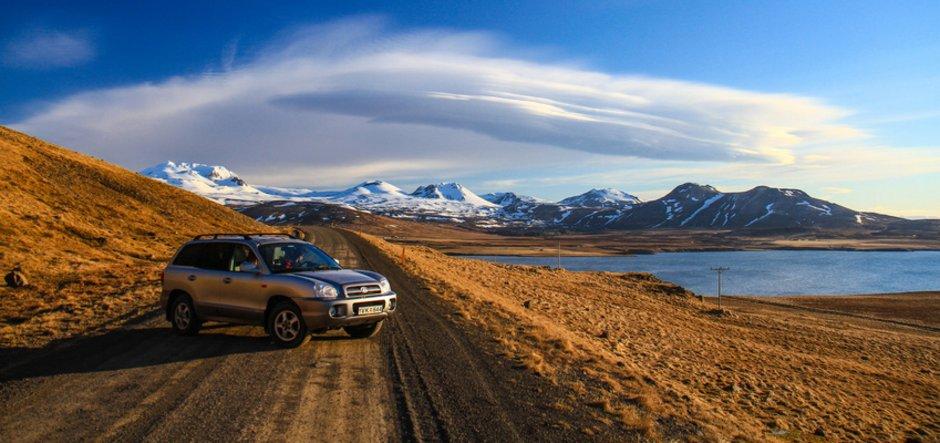Geländewagen auf Feldweg, direkt an einem Gewässer. Im Hintergrund erheben sich Berge unter wolkigem, aber blauen Himmel. Brauntöne, Kreditvergleich, Foto: olivereitel/fotolia.com