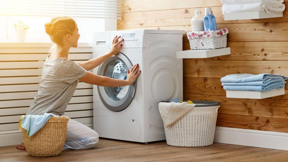 Energiesparen, Frau hockt vor einer Waschmaschine, Foto: JenkoAtaman/stock.adobe.com