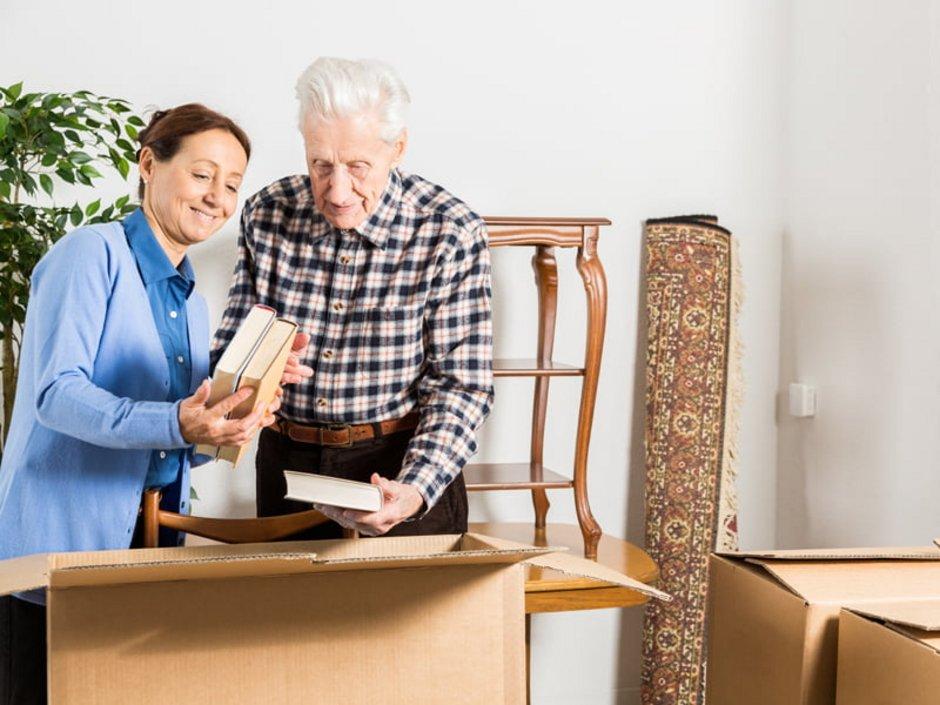 Haushaltsauflösung, Aussortieren, Entrümpeln, Frau packt mit älterem Mann Bücher in einen Karton, Foto: iStock/FredFroese