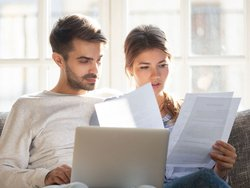 Heizkostenabrechnung prüfen, Mann und Frau sitzen am Laptop und prüfen Dokumente, Foto: fizkes / stock.adobe.com