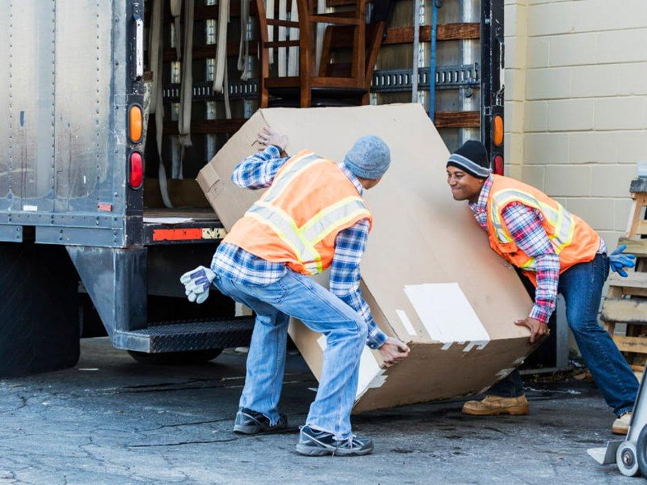 Haushaltsauflösung, Unternehmen, Zwei Männer in Warnwesten laden einen großen Karton in einen Laster, Foto: iStock.com/kali9