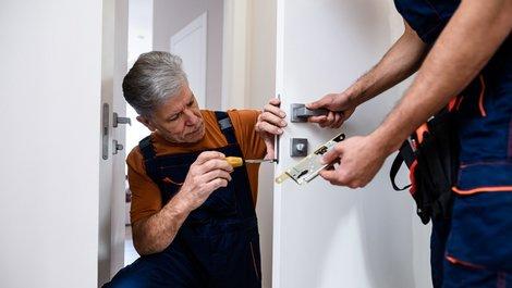 Handwerker wechseln ein Türschloss, Foto: istock.com / LanaStock