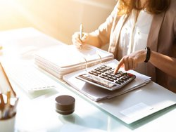 Mieterhöhung, Bild von einer Frau, die mit einem Taschenrechner vor einem dicken Ordner sitzt und etwas ausrechnet, Foto: Andrey Popov / stock.adobe.com
