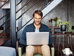 Mängelanzeige, Mann sitzt mit Laptop auf seinem Schoß in einem Sessel, Foto: iStock.com / kupicoo