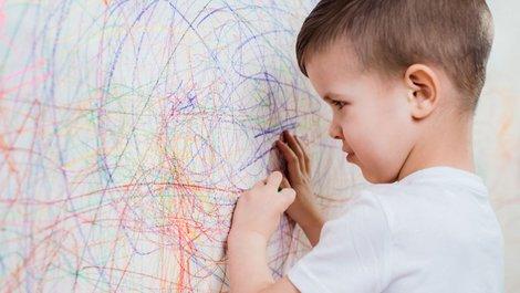 Ausmalen beim Auszug, ein Foto mit einem kleinen Jungen, der eine weiße Wand mit Buntstiften anmalt, Foto: iStock.com / JohnAlexandr