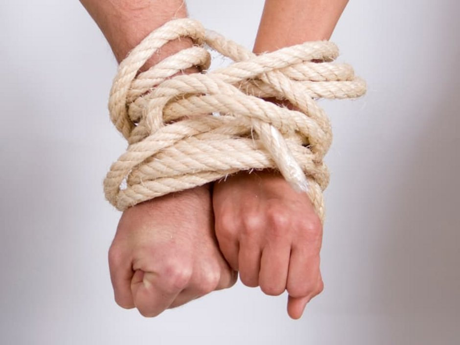 Immobilie geerbt, Immobilie erben, Wohnung erben, Haus erben, Erbengemeinschaft, zwei Hände sind mit einem Seil aneinander gefesselt, Foto: iStock.com/Cirilopoeta