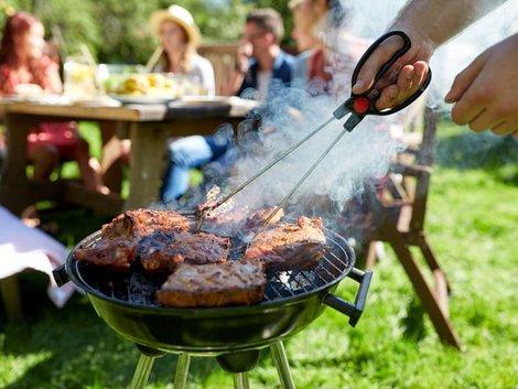 Grillen, Rasenmähen, Nacktsonnen, Mann grillt Steaks und Rauch steigt auf, im Hintergrund sitzen Menschen, Foto: Syda Productions/stock.adobe.com