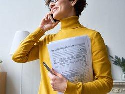 Mieteinnahmen versteuern, Bild von einer Frau, die telefoniert und ein Formular in der Hand hält, Foto: iStock.com / mediaphotos